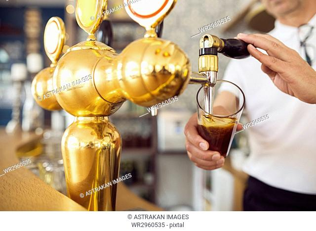 Bartender pouring beer into beer glass