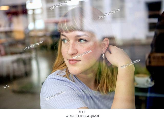 Portrait of young woman in a cafe looking out of window