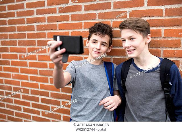 Schoolboys (12-13) taking selfie with mobile phone in front of building