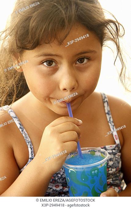 Little girl eating an iced drink