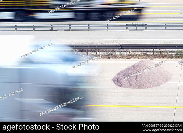 27 May 2020, Saxony-Anhalt, Barleben: Trucks drive on the Autobahn 2 near the state capital past a pile of gravel in a section set up for a construction site