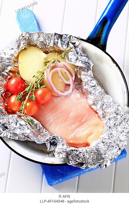 Raw chicken breast and vegetables in tinfoil