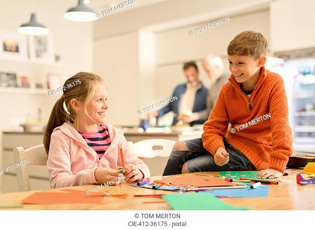 Brother and sister doing crafts at table