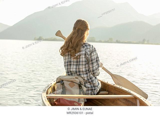 Back of female traveler on a canoe