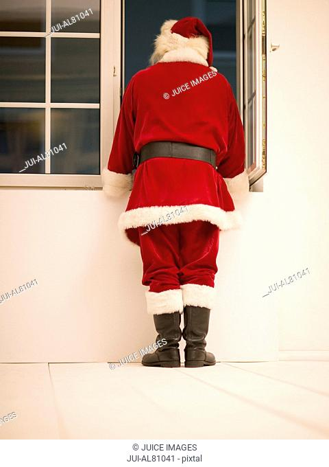 Rear view of Santa Claus looking out window