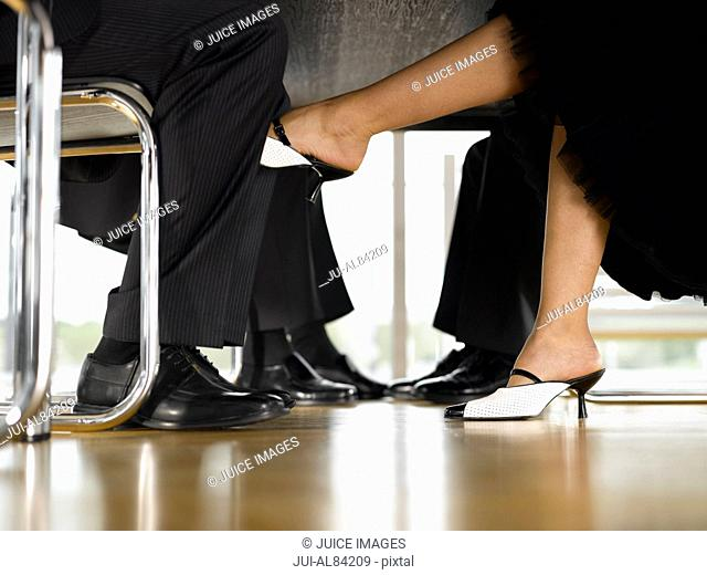 Businesswomanis foot touching businessmanis leg under table