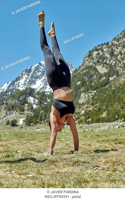 Young woman doing yoga in nature, handstand on meadow