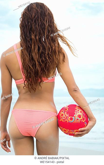Backside of attractive woman in bikini holding a volleyball at a beach