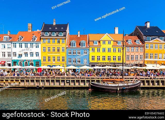 COPENHAGEN, DENMARK - JULY 25: Nyhavn district is one of the most famous landmark in Copenhagen. People enjoy sunny weather in open cafees in Copenhagen on July...