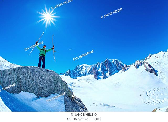 Mature male skier holding up ski's on Mont Blanc massif, Graian Alps, France