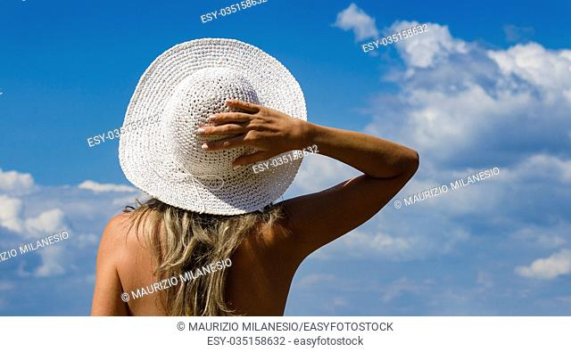 Young girl turned back, holding her hat with her hand behind her head, looking at a cloudy blue sky