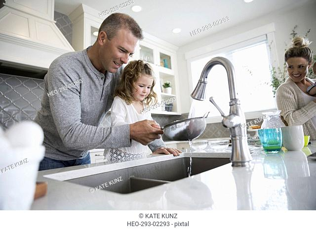 Father and daughter washing berries in kitchen sink