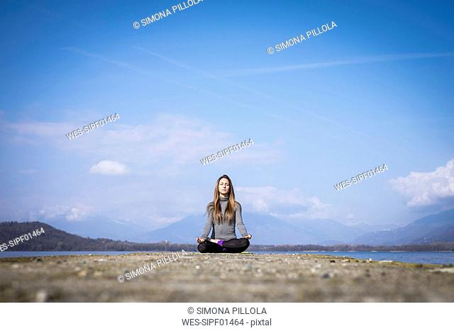 Woman practicing yoga on a pier at a lake