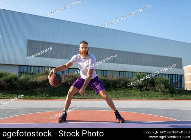 Determined athlete playing streetball on court