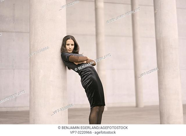 confident woman leaning against pillars, crossed arms, in city Munich, Germany