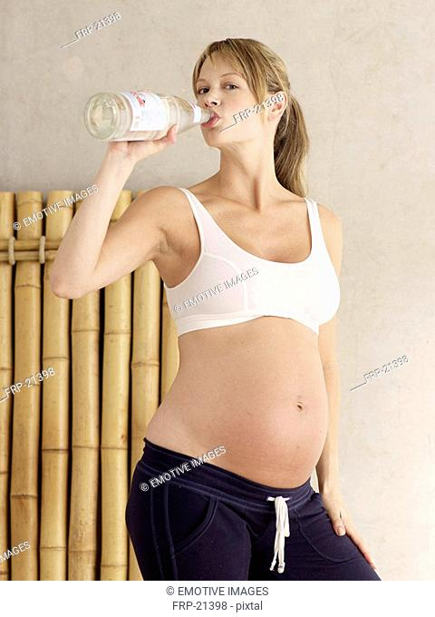 Pregnant woman drinking water from a bottle