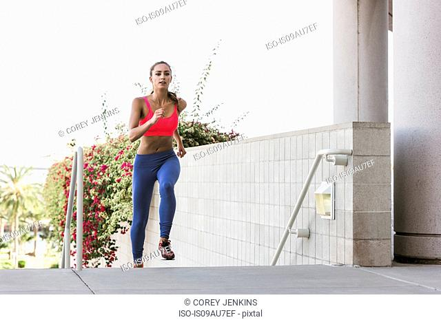 Young woman wearing sports clothing running up stairway looking at camera