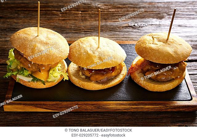 Burger in a row on a slate board and wood table