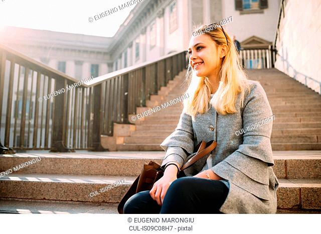 Young woman with long blond hair sitting on stairway, Milan, Italy