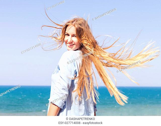 Young blonde woman with fluttering hair on the background of the ocean