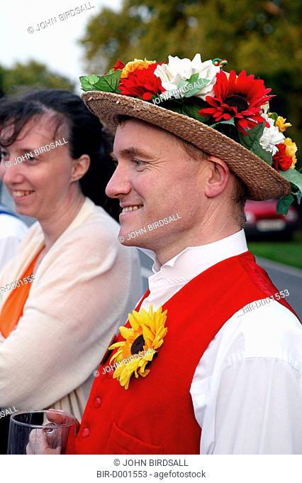 Morris dancer wearing costume standing outdoors smiling