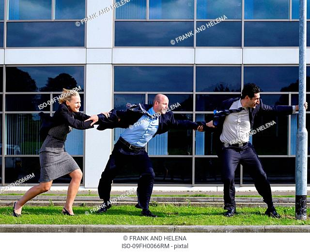 Business people clinging to a lamp post