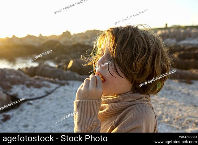 A boy on the beach at sunset, having a snack