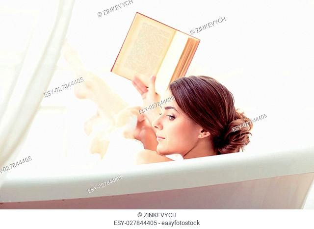 Weekend for myself. Rear view of beautiful young woman looking over her shoulder and holding a book while enjoying bubble bath