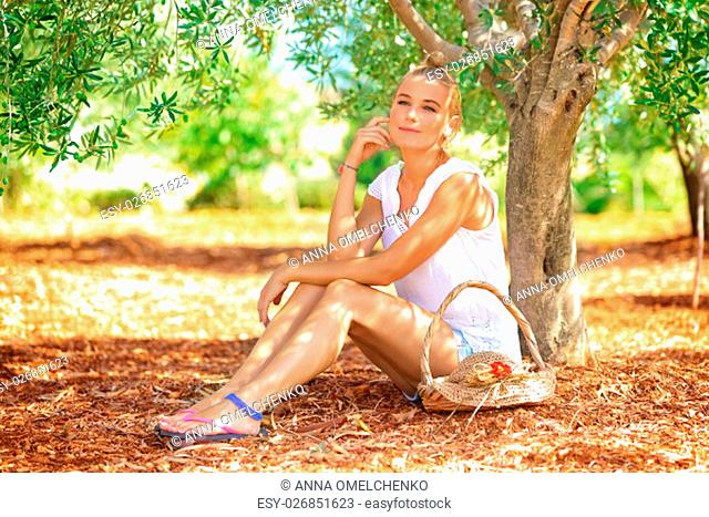 Beautiful woman in olive garden, sitting near olive tree and resting, relaxation in a countryside, enjoying autumn harvest season