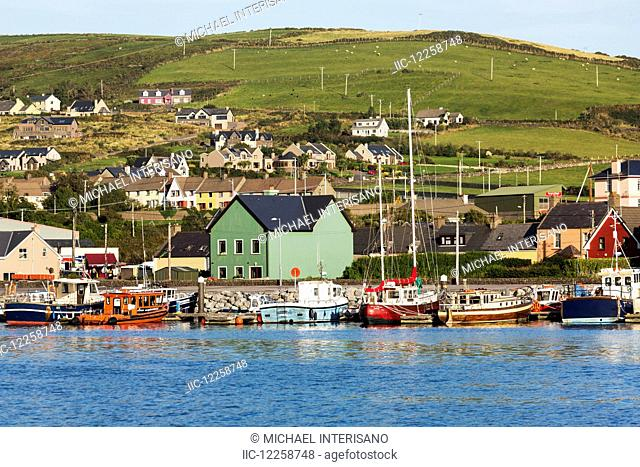 Colourful boats and houses lining a harbour with hilly pastures and blue sky; Dingle, County Kerry, Ireland