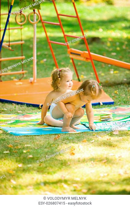 The two little baby girls playing at outdoor playground against green grass