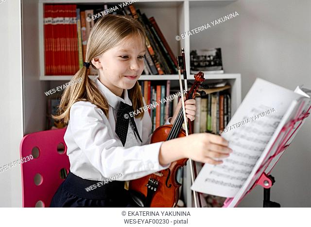 Smiling girl with violin looking at notes on the music stand