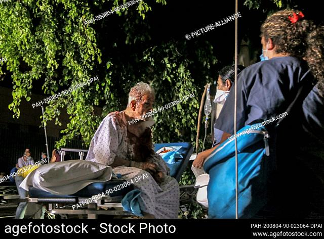 04 August 2020, Lebanon, Beirut: A wounded elderly man waits to receive treatment at the parking lot of Al Roum Hospital