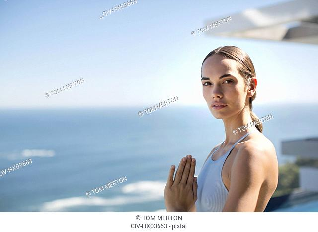 Portrait serene woman practicing yoga with hands at heart center on sunny patio with ocean view