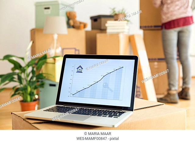 Rising line graph on laptop screen in front of cardboard boxes in a new home