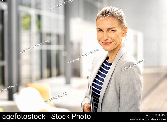 Smiling female professional holding digital tablet