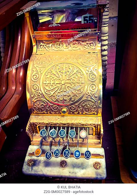 An ornate cash register with a few keys and an embossed, metal dome in a curio shop, Canada. Such machines were widely used throughout Canada and USA during the...