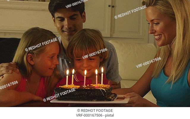 Medium shot of boy blowing out birthday candles, Sotogrande, Spain