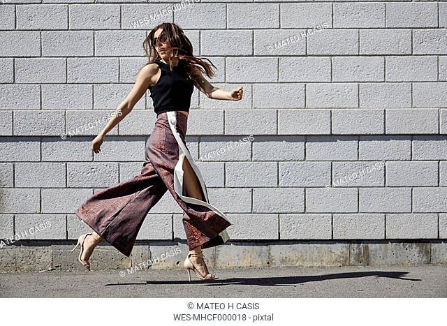 Fashionable young woman passing brick wall
