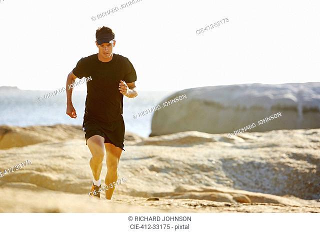 Male triathlete running on sunny rocky trail