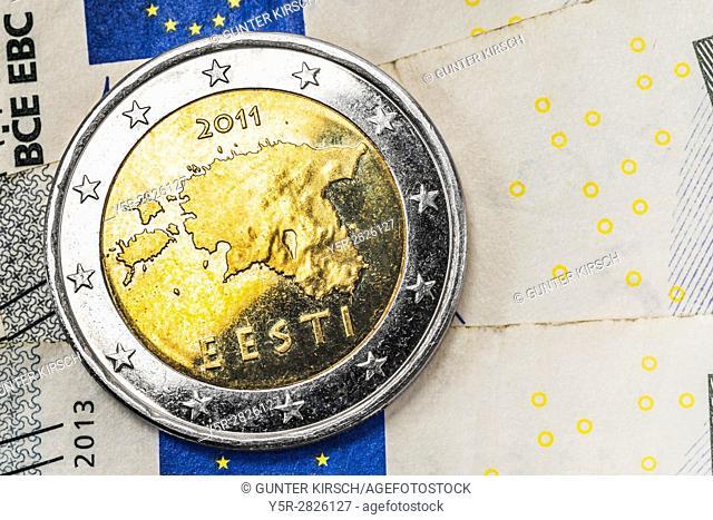 a 2 euro coin from Estonia on euro banknotes