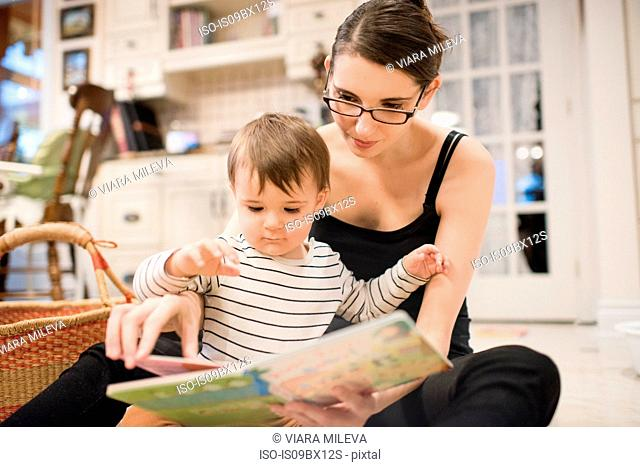 Baby boy and mother reading on floor