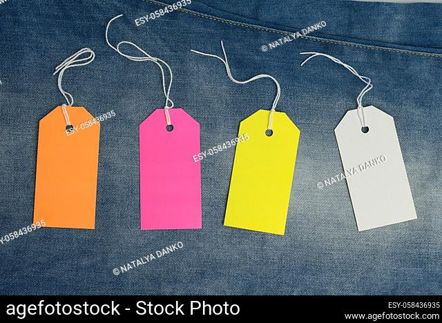 blank rectangular cardboard colored tags on blue jeans background, top view
