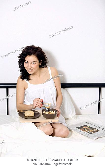 Brunette beautiful woman having breakfast in bed