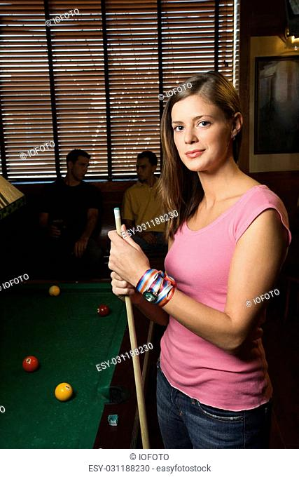 Portrait of woman standing by billiards table holding pool stick