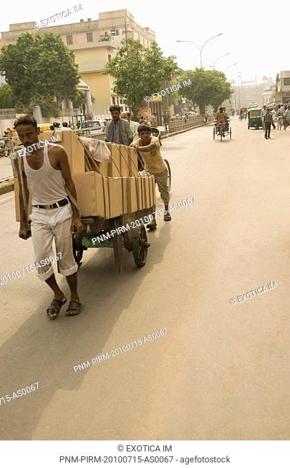 Workers pulling a cart on the road, Chandni Chowk, Delhi, India