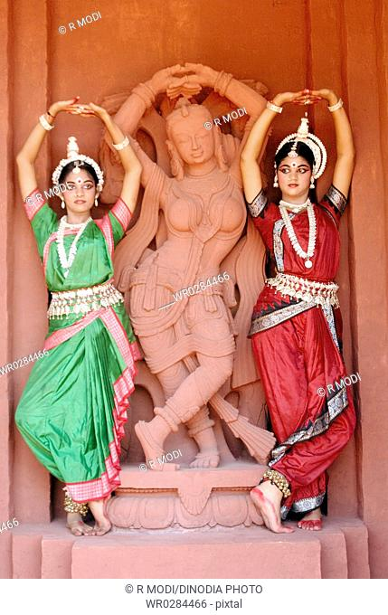 Women performing classical traditional Odissi dance in front of statue on stage MR736C,736D