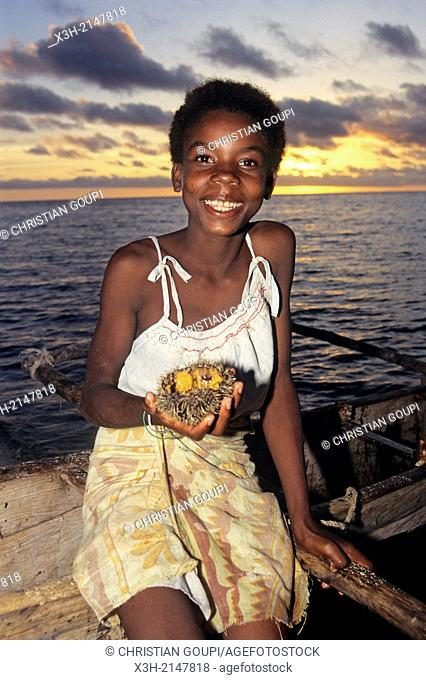 little girl holding sea urchin at the seaside at sunset, Tulear, Madagascar, Indian Ocean, Southeast Africa