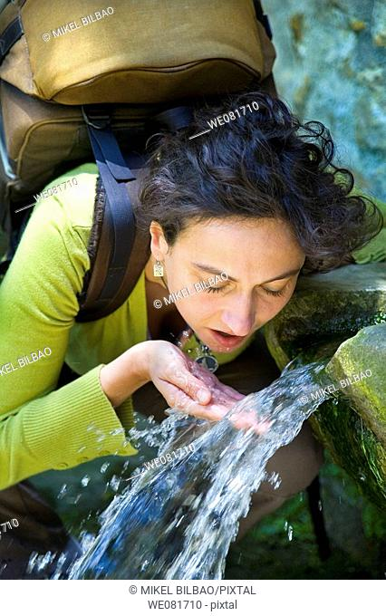 Portrait of a young woman with a backpack drinking in a fountain