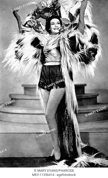 Dorothy Compton, performer, appearing in an elaborate costume at the French Casino (probably the one in New York City), in Movie Humor magazine, November 1937